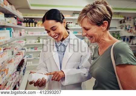 Smiling Senior Customer With Pharmacist Looking For Medicinal Details On Bottle Standing Near Shelve