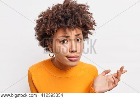 Headshot Of Puzzled African American Woman Looks With Indignant Expressio At Camera Listens Attentiv