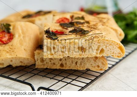 Slice Of Chopped Focaccia, Pizza, Cut Flat Bread With Vegetables On Grid, Tradition Italian Cuisine.
