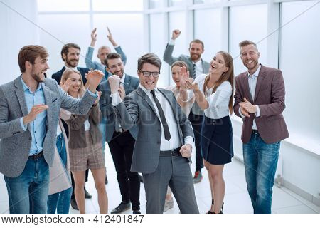 triumphant business team congratulating their leader. success concept