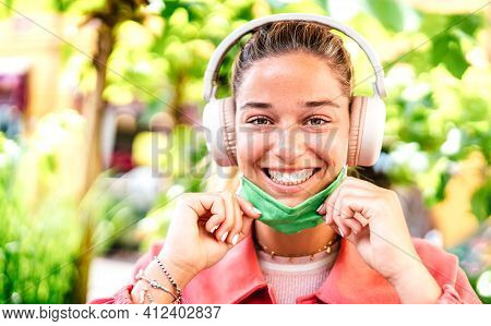 Young Woman Smiling Looking At Camera With Open Facial Mask And Headphones - New Normal Lifestyle Co