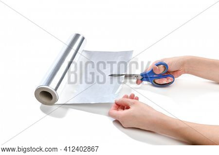 Lifehack; female hand cutting aluminum foil to sharpen scissors isolated on white background