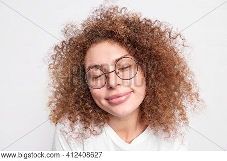 Close Up Shot Of Pleased European Woman With Curly Bushy Hair Closes Eyes From Pleasure Recalls Nice