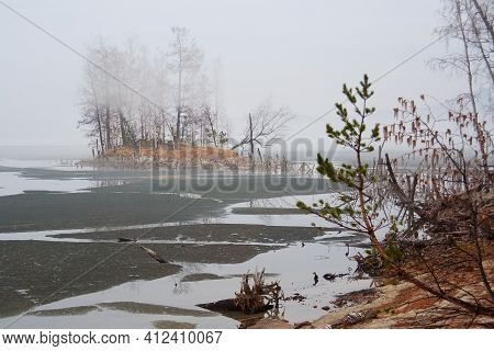 Ice In Peaceful Calm Still Water Along The Lake Near A Pine Tree Forest