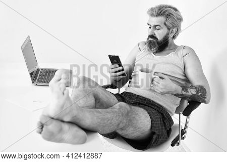 Multitasking. Relaxed Man Sit On Comfortable Chair Using Laptop. Online In Social Media. Working Bar