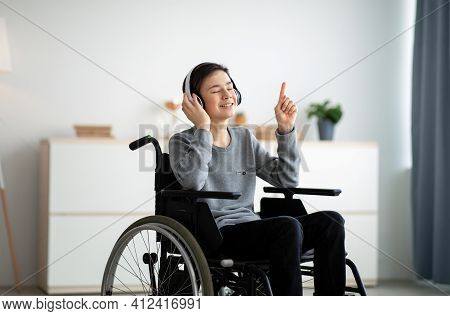 Happy Handicapped Teen Boy In Wheelchair Listening To Music With Closed Eyes, Using Headphones At Ho
