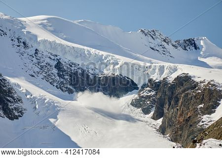 Snow avalanche on a glacier high in the mountains