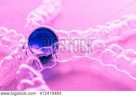 Invisible Aligner Teeth Retainers On A Purple Background