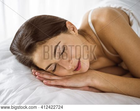 Beautiful Young Brunette Woman Sleeping While Lying In Bed Comfortably And Blissfully. Good Morning