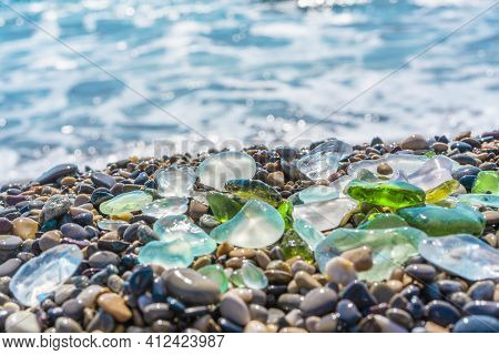 Natural Polish Textured Sea Glass And Stones On The Seashore. Azure Clear Sea Water With Waves. Gree
