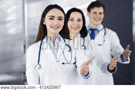 Doctors Are Standing As A Team While Offering Their Helping Hands For Shaking Hand Or Saving Peoples