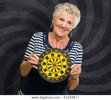 Happy Mature Woman Holding Dart Board On Wall
