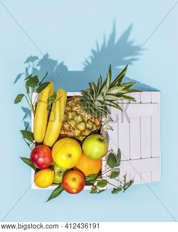 Fresh Tropical Fruits In A Wooden Box With Dark Shadows On A Blue Background. Local Market, Farm Fru
