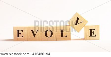 On A Light Background, Wooden Cubes With The Text Evolve