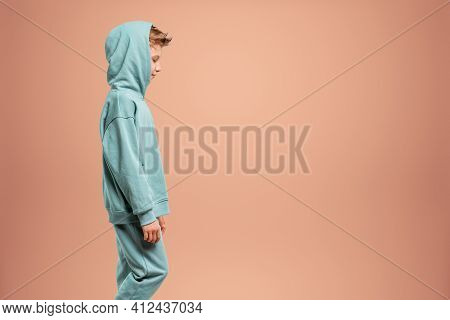 A Boy In A Turquoise Suit Posing And Fooling Around On A Beige Background, Looking At The Camera. Ch