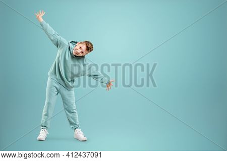 Little In A Turquoise Suit Poses And Fools Around On A Turquoise Background, Looks At The Camera. Ch