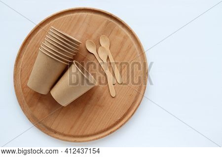 Kraft Paper And Wooden Kitchen Utensils On Wooden Cutting Board On Table. Recycled And Sustainable P