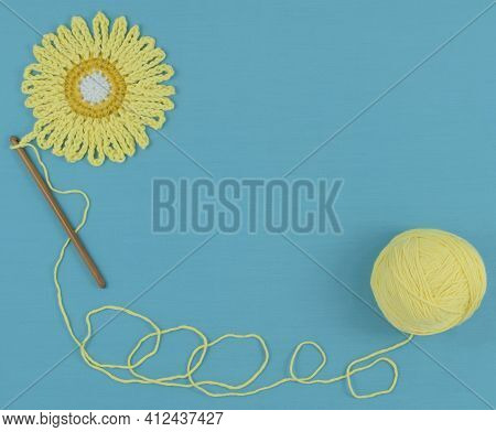 Blue Textile Background With A Crocheted Element, A Crochet Hook, And A Ball Of Thread.