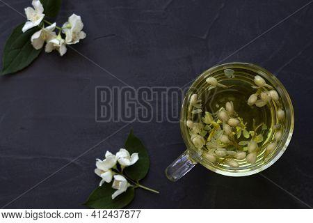 Cup Of Jasmine Tea. Cup Of Hot Herbal Tea With Jasmine Fresh Flowers On A Black Table. Healthy Lifes