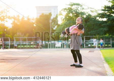 Happy Family To Spend Time Concept. Mom Played Happily With Her Daughter. Mother Held Girl And Float