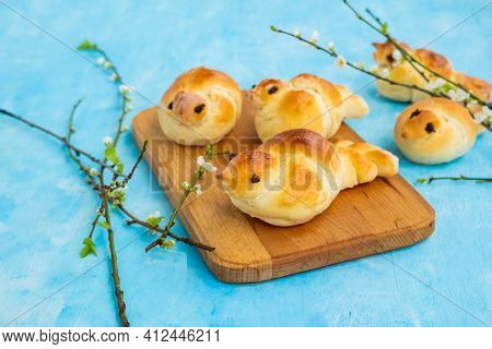 Traditional Yeast Buns In The Form Of Larks On A Wooden Board Against A Blue Concrete Background.