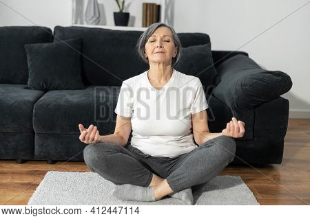 A Peaceful And Calm Senior Female Practicing Yoga At Home, An Older Woman Sits In Lotus Position, A