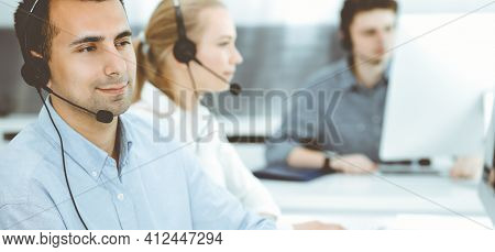 Call Center. Group Of Casual Dressed Operators At Work. Adult Businessman In Headset At Customer Ser