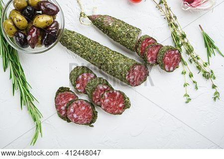 Traditianal Fuet Sausage In Herbs With Ingredients On White Surface, Top View.