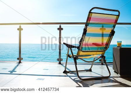 The Balcony With Chaise Lounge On Background Of Seaside View.
