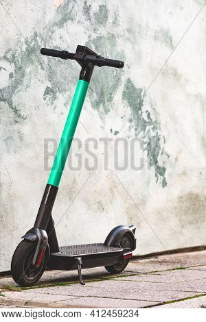 Electric Scooter Standing Against Bright Wall Background. E-scooter Or Kick Scooter Using With Mobil