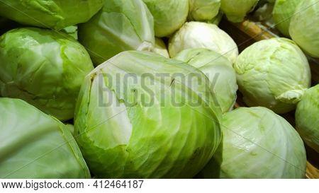 Pile Of Cabbage On Supermarket Shelves For Sale. Vegetables Background. Fresh Food. Brassica Olerace