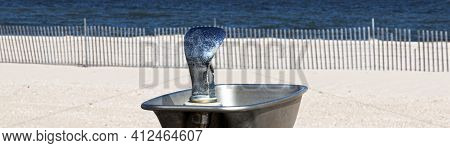 Horizontal View Of The Top Of A Water Fountain At The Beach With A Beach Fence And The Long Island S