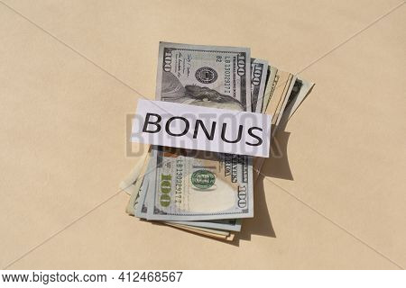 Cash Dollars Money On Beige Background And The Word Bonus . Concept Of Bonus