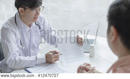 Young Asian man in a white robe talks to a man, Doctors diagnose diseases and give advice or treatme