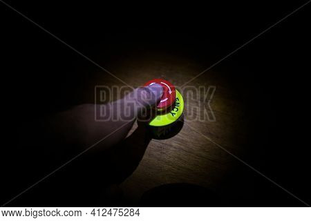 Hand Press On Big Red Button Grounge Background. Red Button On Table In Dark Low Key Background.