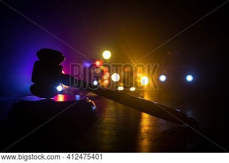 Law Theme, Mallet Of The Judge On Wooden Desk . Silhouette Of Police Cars On Backside. Law Gavel On