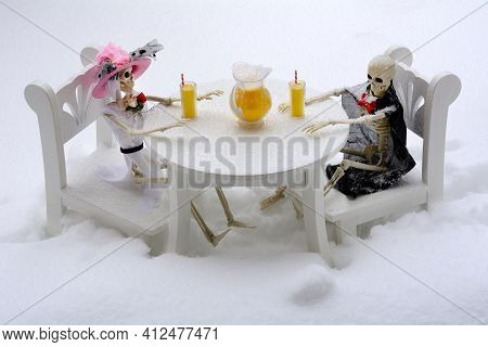 Lemonade Party Refreshment Party Among Skeleton Couple Sitting In Chairs At Table In Snow Storm