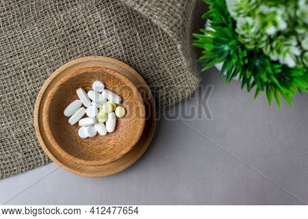 A Handful Of Pills In A Wooden Plate With Green Plant On Burlap. The Concept Of Medcine, Treatment.