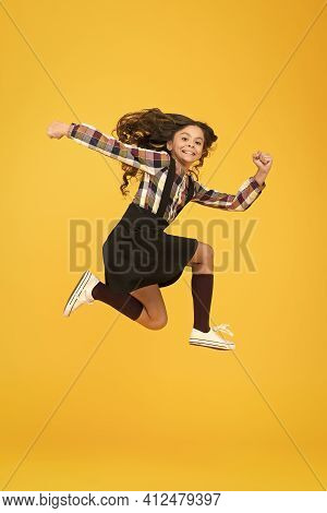 Feel Inner Energy. Girl With Long Hair Jumping On Yellow Background. Carefree Kid Summer Holiday. Ti