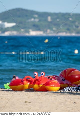 Family Summer Vacation On French Riviera, France, View On Blue Sea, Sandy Beach And Red Inflatable F