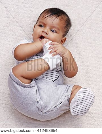 Cute Indian Baby Boy Lying On A Soft Baby Towel And Biting Own Feet