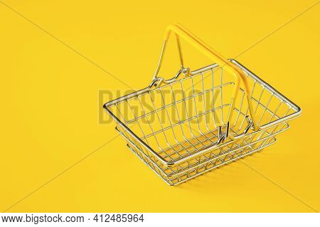 Empty Metal Wire Shopping Basket With Yellow Handles Isolated On Yellow Background. Consumerism Conc