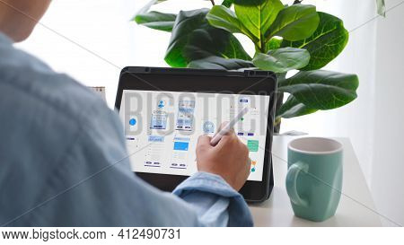 Man Hand Holding Digital Tablet With Mobile App Development Prototype While Working At Home