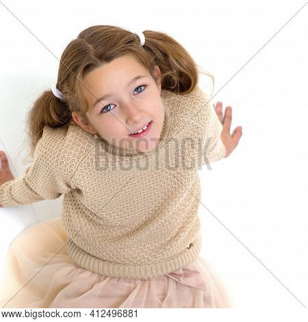 Happy Preteen Girl Sitting On Floor Leaning Back On Hands. Beautiful Smiling Girl With Pigtails Wear