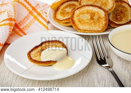 Checkered Napkin, Plate With Pancakes, Pancake Poured Condensed Milk In White Saucer, Fork, Bowl Wit