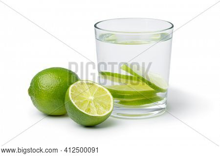 Fresh green limes and glass of water with lime slices as a healthy drink isolated on white background