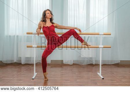 A Choreographer In A Red Jumpsuit Is Engaged Near The Machine, In The Choreographic Hall.