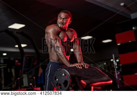 Trained And Muscular Sportsman Poses To The Camera Without Shirt. African American Athlete With Perf