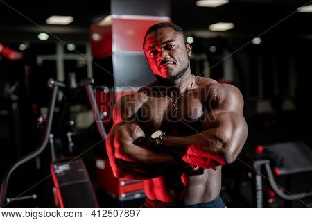 Athlete With Strong Body Poses Cross Hands On Modern Gym Background. Front View On Very Muscular Pum