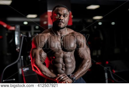 Strong Handsome Fitness Trainer Poses With Modern Sport Gym Interior On Background. Naked Torso With